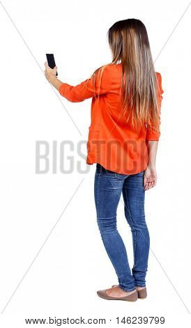 back view of standing young beautiful woman using a mobile phone. girl watching. girl in a red jacket stands sideways and take pictures on the phone.