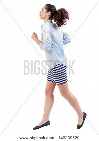 side view of running woman. beautiful girl in motion. Swarthy girl in a checkered dress runs in the side and looking up.