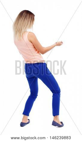 back view of standing girl pulling a rope from the top or cling to something. Isolated over white background. The blonde in a pink shirt pulling rope.