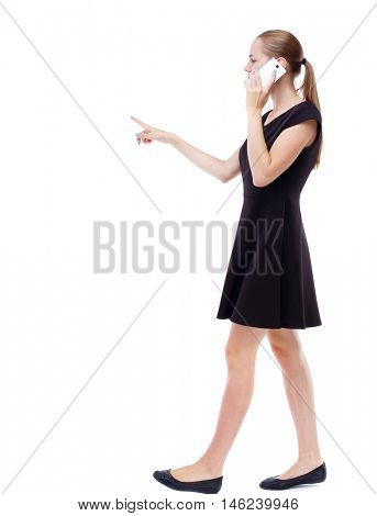 side view of walking woman. beautiful girl going, pointing and talking on smartphone. Isolated over white background. Blonde in a short black dress and is talking on the phone is pointing forward.