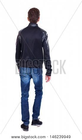 Back view of going handsome man. walking young guy . Curly guy in a black leather jacket goes away.