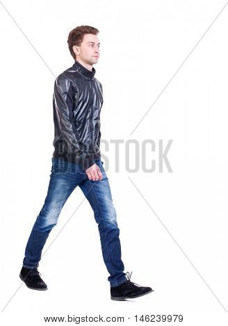 Back view of going handsome man. walking young guy . Curly guy in a black leather jacket comes to meet us.