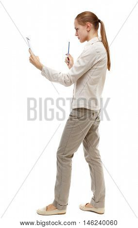 back view of stands woman takes notes in a notebook. Isolated over white background. Skinny girl in white denim suit reads the information in a notebook.