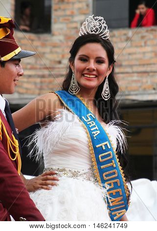 Cajamarca Peru - February 8 2016: Attractive beauty queen with white dress and tiara smiles in Carnival parade in Cajamarca Peru on February 8 2016