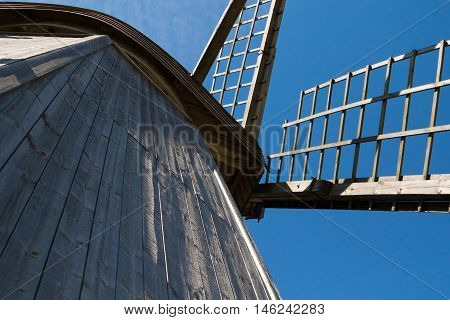 Wooden windmill piece on blue sky background
