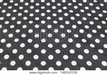 Closeup surface fabric pattern at old and wrinkled black fabric handkerchief with white circle dot texture background