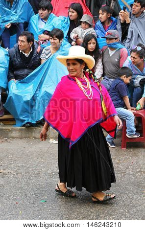 Cajamarca Peru - February 8 2016: Senior Andean woman in bright pink poncho and sombrero walks in front of audience in Carnival parade in Cajamarca Peru on February 8 2016