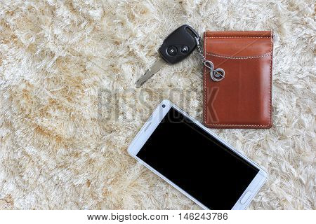 Mobile phone whit car key and brown wallet on brown shaggy carpet