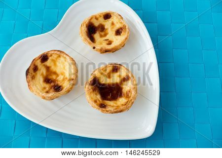 Homemade Portuguese egg tart pastry pastel de nata on a white heart shaped plate isolated on blue background.
