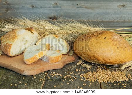 whole and sliced bread with ears and wheat grain on wooden background