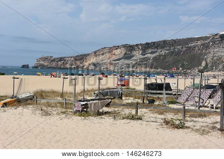 NAZARE, PORTUGAL - AUG 24: Drying fish on the beach at Nazare fishing village in Portugal, as seen on Aug 24, 2016. It has become a tourist attraction, advertising as a picturesque seaside village.