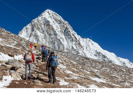 Group Of Trekkers Coming Up To Kala Patthar - The Everest Mount View Point - With Pumori Peak On The