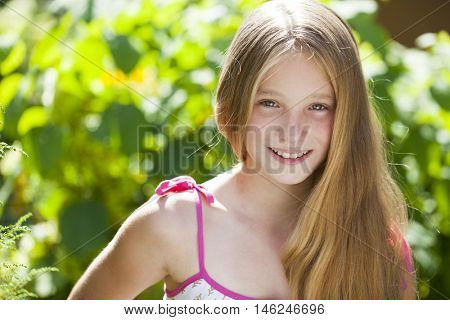 Portrait of a beautiful young blonde little girl on the background of summer park
