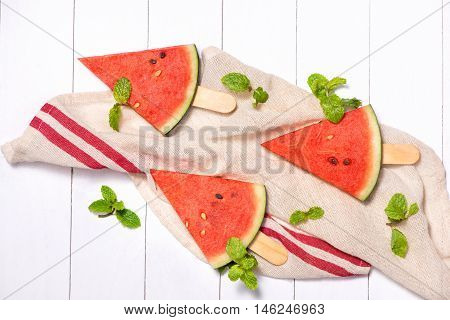 Watermelon slices on sticks. Watermelon popsicle on wooden white background. Top view flat lay