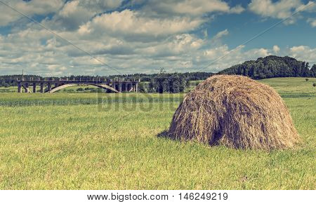 Countryside landscape with haystack and field of grass as foreground
