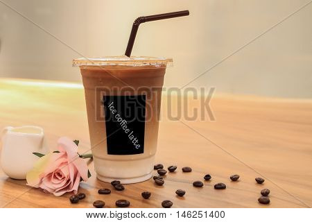 Iced coffee latte on wood table whit pink rose