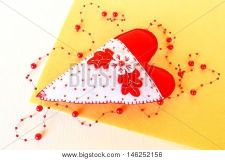 Handmade felt heart with flowers. Symbol of Valentines Day, felt white and red heart decor on yellow background
