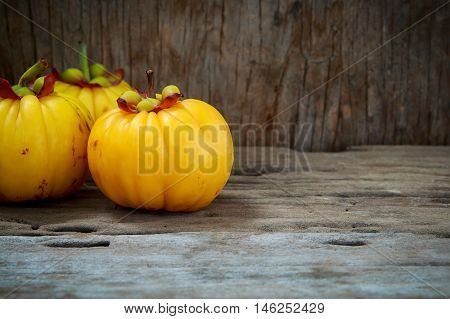 Garcinia Cambogia Fruit On Wood Background.  Fruit For Diet And Good Health.
