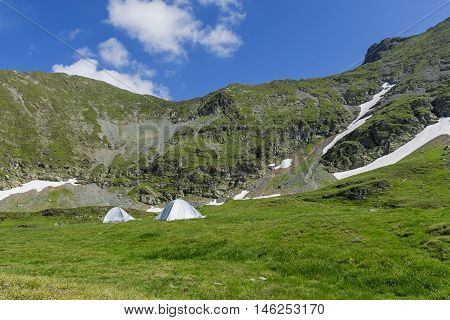 Mountain landscape with camping tents under the summit