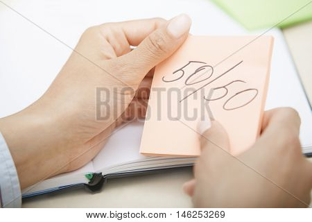 Hands holding sticky note with equal chances