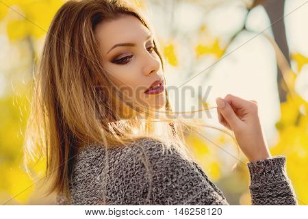 Closeup outdoors portrait of beautiful young blonde Caucasian woman wearing makeup and gray sweater, on sunny day in park in autumn. Retouched, natural light.