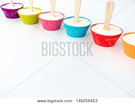 Colorful cupcake cases with a wooden ice lolly stick in the middle filled with vanilla ice cream.