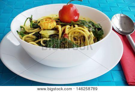 Prawn Laksa Soup in white porcelain bowl on blue place mat.