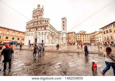 Lucca, Italy - June 03, 2016: People walk on the main square with San Michele church in Lucca old town in Italy