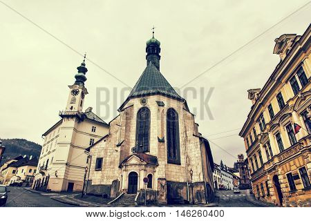 Saint Catherine's church and town hall in Banska Stiavnica city Slovak republic. Cultural heritage. Architectural scene. Retro photo filter. Place for worship. Streets and buildings.