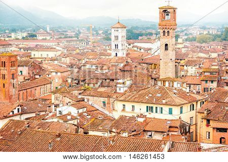 Aerial cityscape view on the old town of Lucca with bell tower San Michele basilica at the foggy weather in Italy