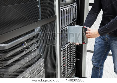 Midsection of male computer engineer installing blade server in chassis at data center