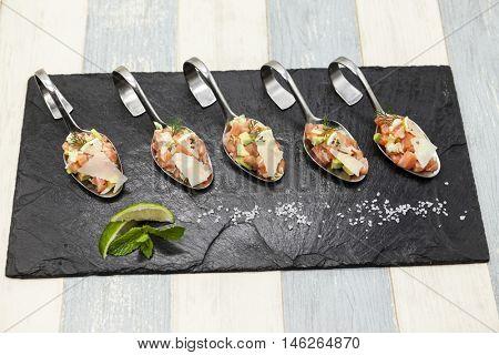 Fresh tartar Norwegian salmon on a small spoon on a black plate.