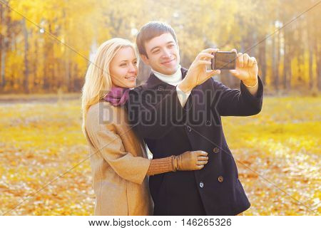 Happy Smiling Young Couple Together Taking Picture Self Portrait On Smarphone In Sunny Autumn Day