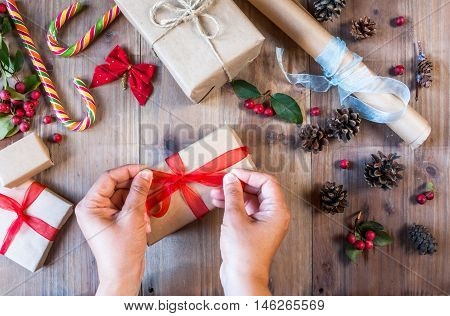 Girl decorates Christmas gift, ties red bow. On the table other gifts. Hands in picture, top view