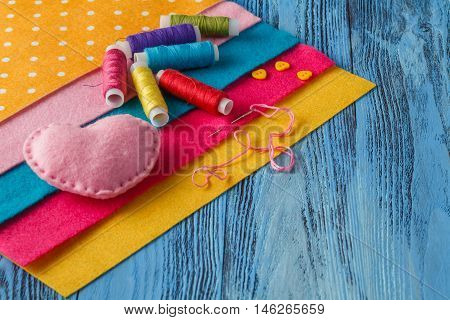 Felt Heart, Threads And A Needle, Sheets Of Felt  - Sewing Set On A Blue Wooden Background With Copy