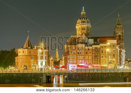 Night city view of Amsterdam canal and Basilica of Saint Nicholas Holland Netherlands.