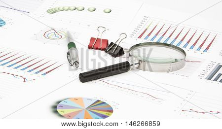 Business still-life diagrams, magnifier, pen and paperclip