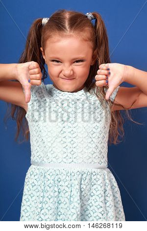 Fun Grimacing Kid Girl Showing Thumb Down On Blue Background. Closeup Portrait