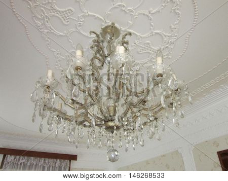 many-tier chandelier on a ceiling of a drawing room the decorated stucco molding