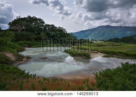 Lake with reflection of the sky and steamy hotsprings in Uzon Caldera, Kamchatka, Russia