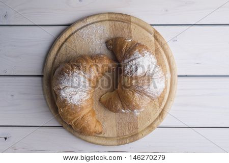 Fresh golden croissants on white wooden table. Country style.