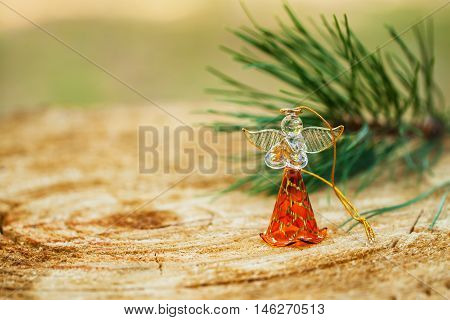 Christmas angel made fromfrom glass with a branch of natural pine on wood background, holiday decorations and backcloths. Place for text. Element for Christmas design.