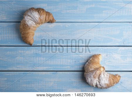 Fresh golden croissants on blue wooden table. Country style.