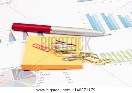Business still-life of a pen, stickers, paperclips, graphs