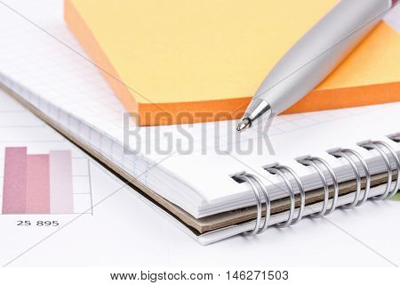 Business still-life of a charts, pen, notepad, stickers