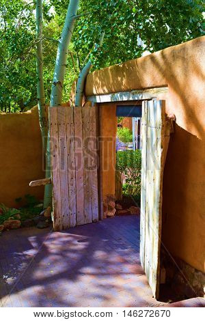 Rustic adobe style wooden door with Spanish Colonial architectural design which opens to a courtyard garden taken in Santa Fe, NM