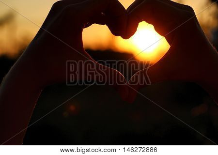 Women's hands are crossed in the form of the heart through which the sun' rays make the way at the sunset.