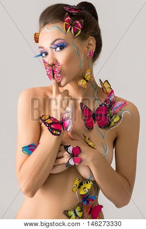 Bodyart. Beautiful nude girl posing with butterflies
