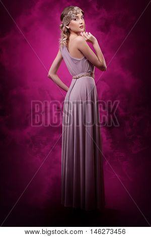 young beautiful woman on a background of pink smoke