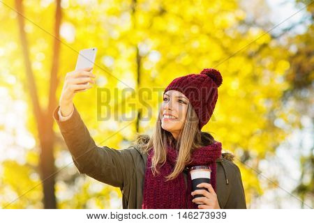 Happy young blonde Caucasian woman in olive green jacket, knitted dark red beanie hat and scarf, holding takeaway coffee, taking a selfie on smart phone, outdoors in autumn. Vibrant colors, retouched.